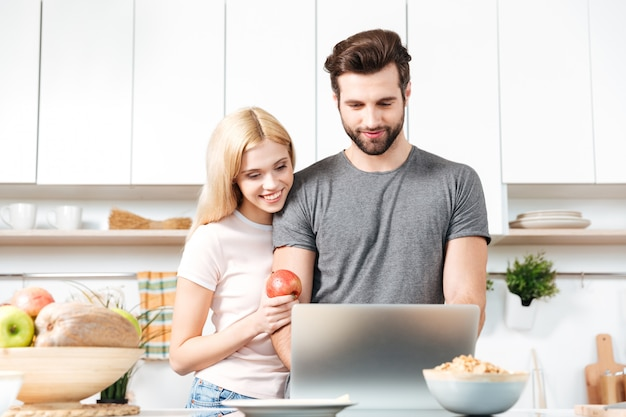Young couple using laptop to look up recipe for their meal