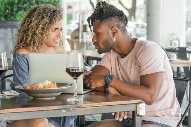 Young couple using a laptop while having lunch together at a restaurant.