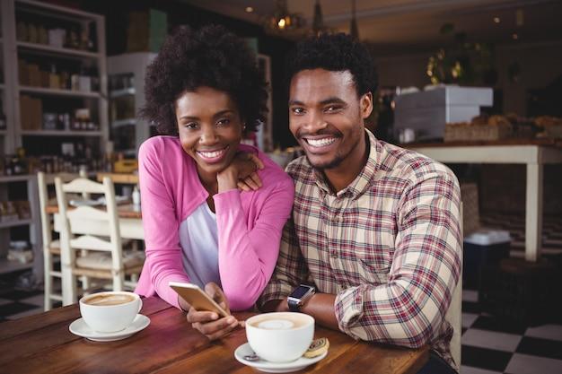 カフェテリアで携帯電話を使用して若いカップル