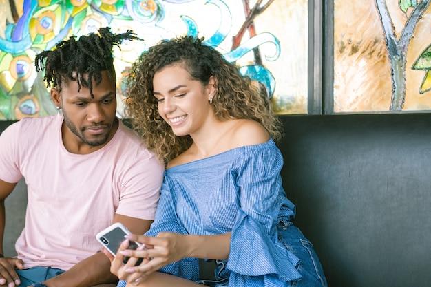 Giovane coppia che utilizza un telefono cellulare e trascorre del tempo insieme in un ristorante.