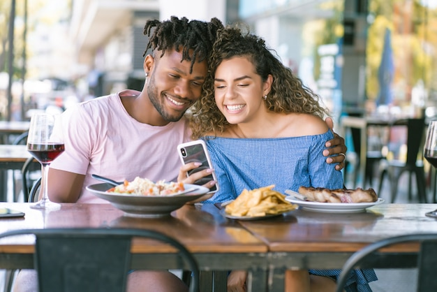 Young couple using a mobile phone and spending good time together while having lunch at a restaurant.