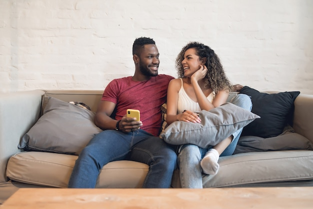Young couple using a mobile phone together while sitting on a couch at home.