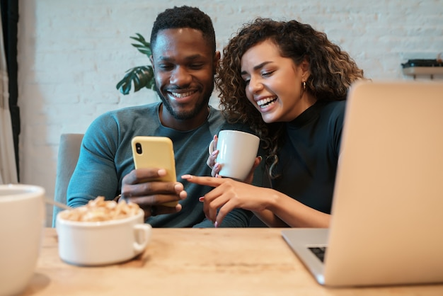 Young couple using a mobile phone while having breakfast together at home.