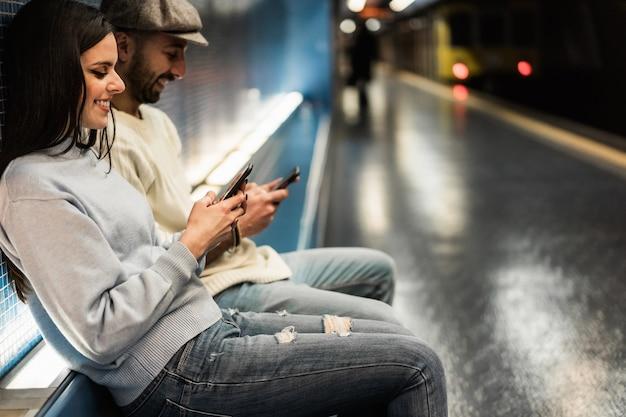 Молодая пара с помощью мобильных телефонов в метро - сосредоточиться на руках девушки