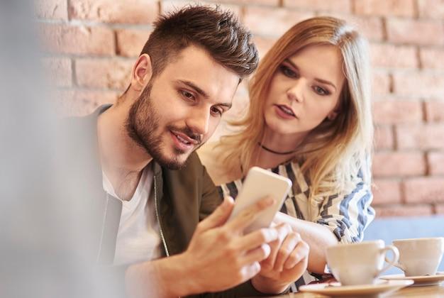 카페 바에서 스마트폰을 사용하는 젊은 부부