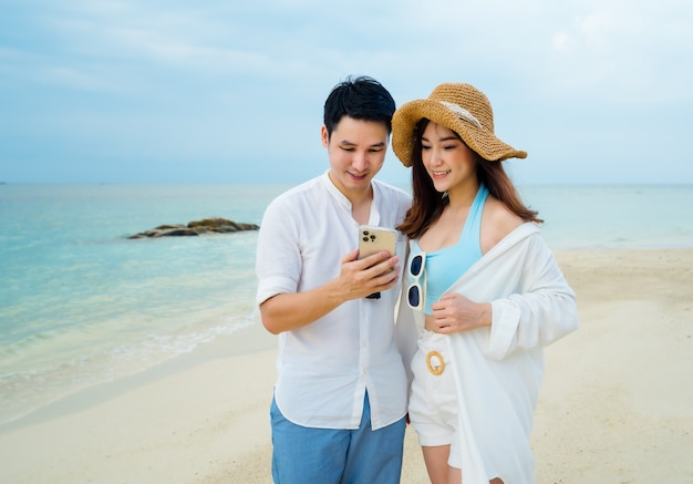 Young couple using smartphone on the sea beach at koh munnork island, rayong, thailand