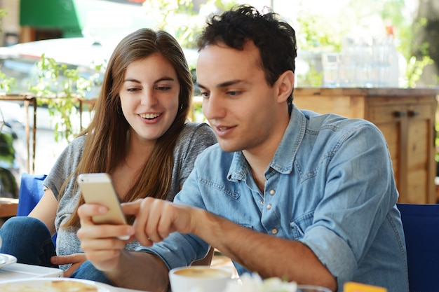 Young couple using smartphone.