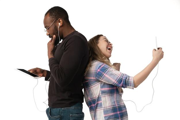 Young couple using smartphones and earphones