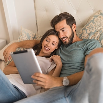 Young couple using tablet on bed