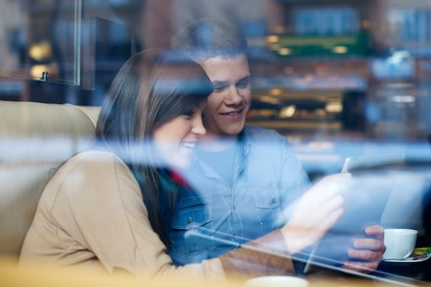 Giovani coppie facendo uso della compressa nella caffetteria