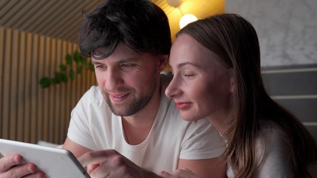 Молодая пара с помощью планшета на кровати в спальне поздно ночью.