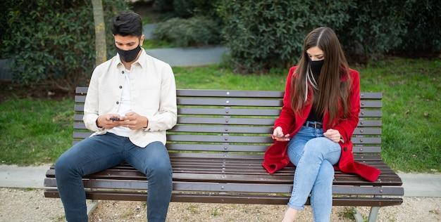 ベンチで携帯電話を使用している若いカップル