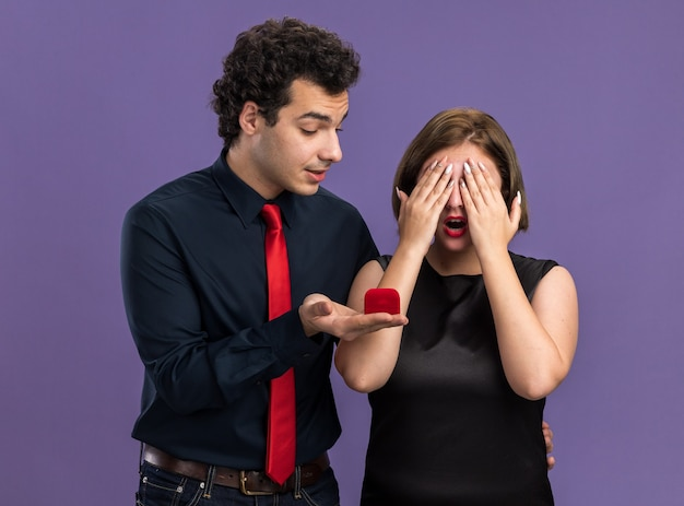 Young couple on valentine's day excited man giving engagement ring to woman looking at ring curious woman covering eyes with hands isolated on purple wall