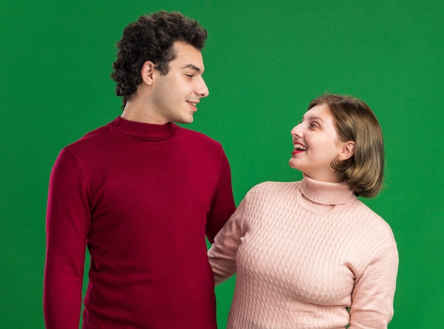 Young couple on valentine's day smiling man joyful woman looking at each other isolated on green wall