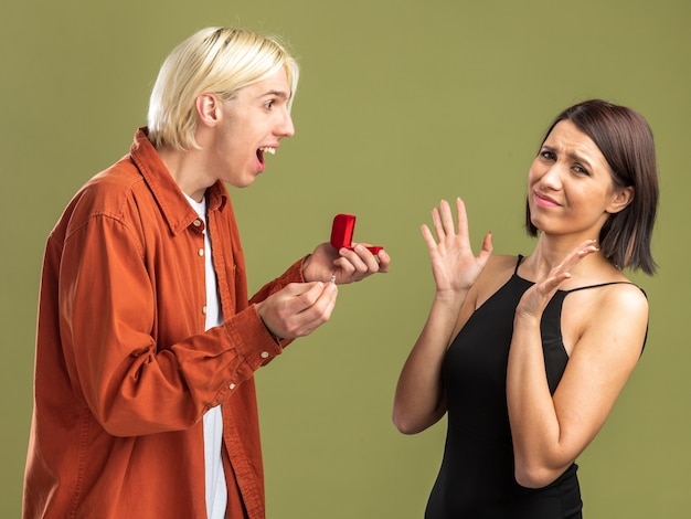 Young couple on valentine's day standing in profile view excited man giving engagement ring to woman and frowning woman showing empty hands  isolated on olive green wall