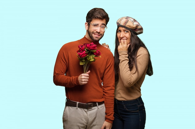 Young couple in valentines day biting nails, nervous and very anxious