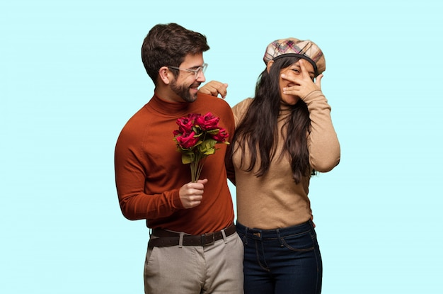 Young couple in valentines day embarrassed and laughing at the same time