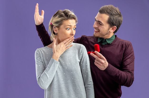 Young couple on valentines day excited guy giving wedding ring to surprised girl isolated on blue background