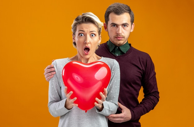 Young couple on valentines day guy standing behind scared girl with balloon isolated on orange background