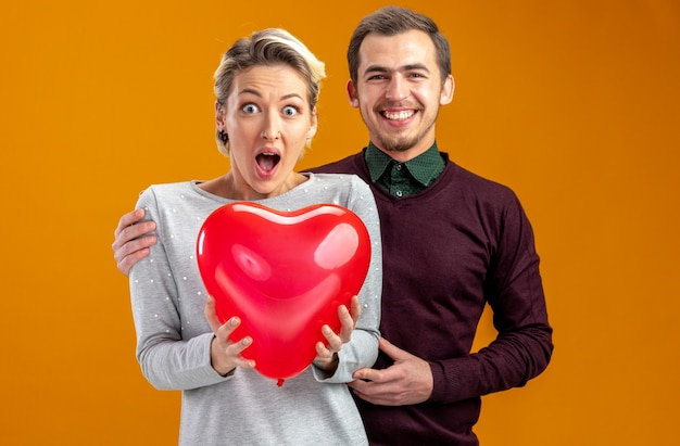 Young couple on valentines day guy standing behind surprised girl with balloon isolated on orange background