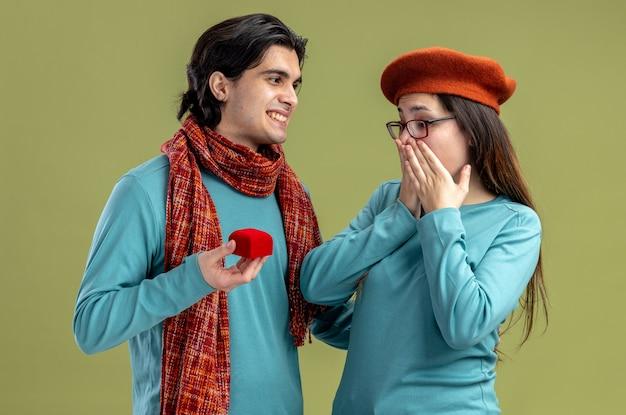 Giovane coppia il giorno di san valentino ragazzo che indossa una sciarpa ragazza che indossa un cappello ragazzo sorridente che dà la fede nuziale alla ragazza sorpresa isolata su sfondo verde oliva