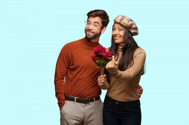 Young couple in valentines day inviting to come