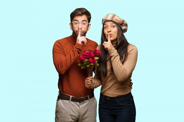 Young couple in valentines day keeping a secret or asking for silence