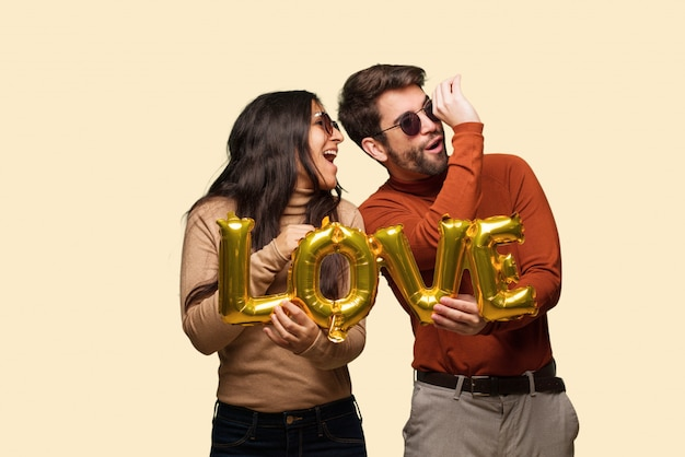 Young couple in valentines day making the gesture of a spyglass