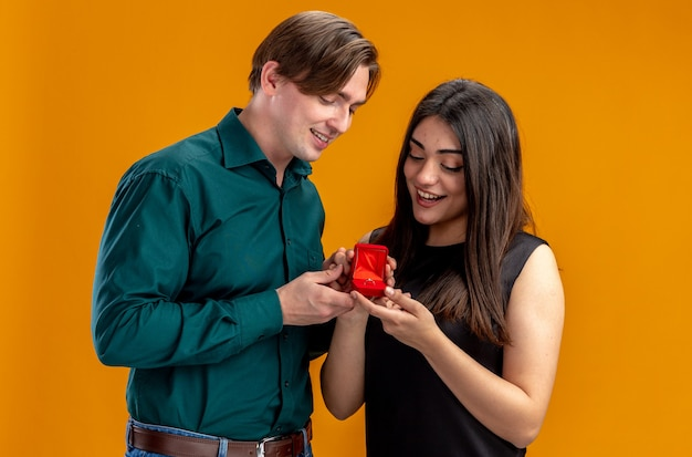 Young couple on valentines day pleased guy giving wedding ring to smiling girl isolated on orange background