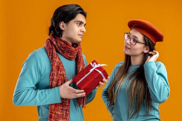 Young couple on valentines day pleased guy wearing scarf holding gift box looking at each other isolated on orange background