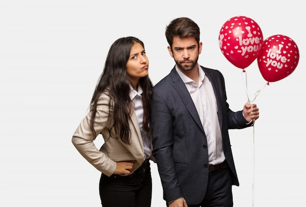 Young couple in valentines day scolding someone very angry