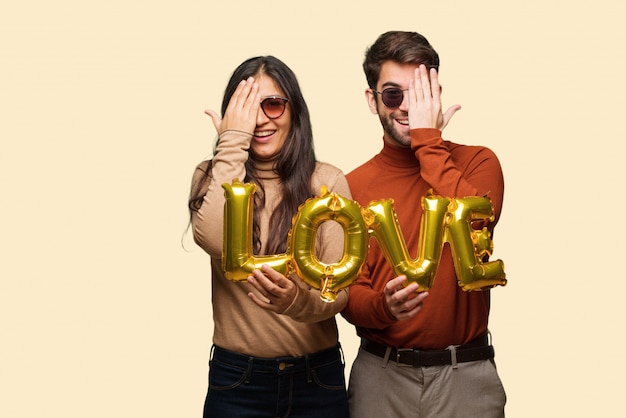 Young couple in valentines day shouting happy and covering face with hand