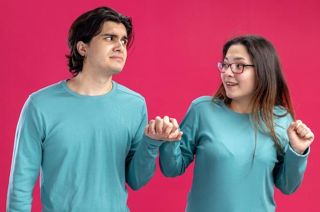 Giovane coppia il giorno di san valentino ragazza sorridente che guarda un ragazzo triste isolato su sfondo rosa pink