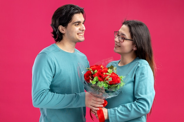 Young couple on valentines day smiling guy giving bouquet to pleased girl isolated on pink background