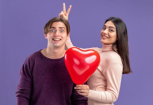 Giovane coppia il giorno di san valentino sorridente che tiene il palloncino del cuore che dà le orecchie da coniglio al ragazzo isolato su sfondo blu