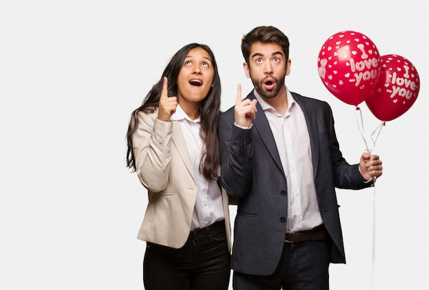 Young couple in valentines day surprised pointing up to show something