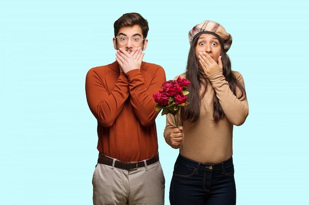 Young couple in valentines day surprised and shocked