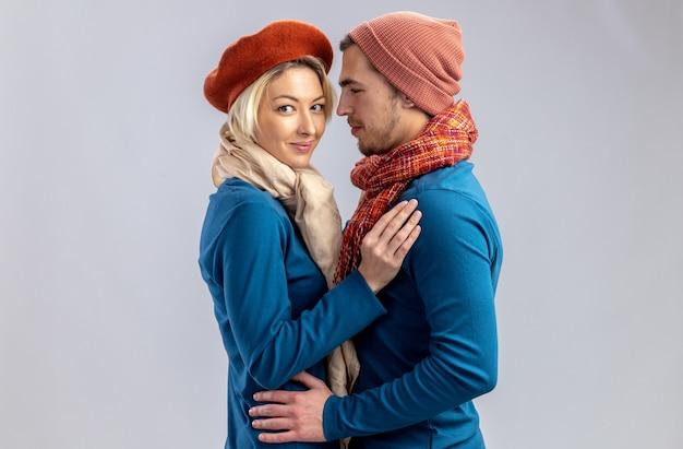 Giovane coppia il giorno di san valentino che indossa un cappello con sciarpa si è abbracciata isolata su sfondo bianco