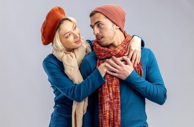 Giovane coppia il giorno di san valentino che indossa un cappello con una sciarpa abbracciata e si guarda l'un l'altro isolato su sfondo bianco