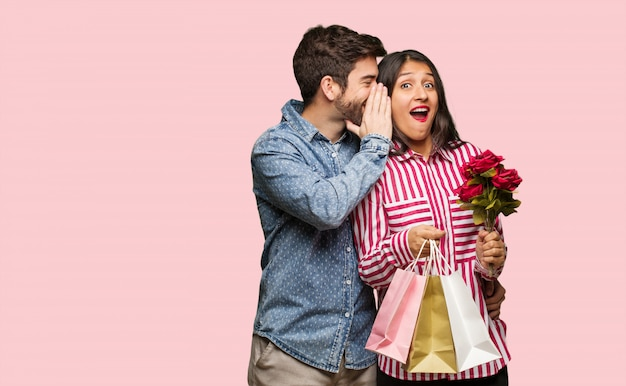 Young couple in valentines day whispering gossip undertone