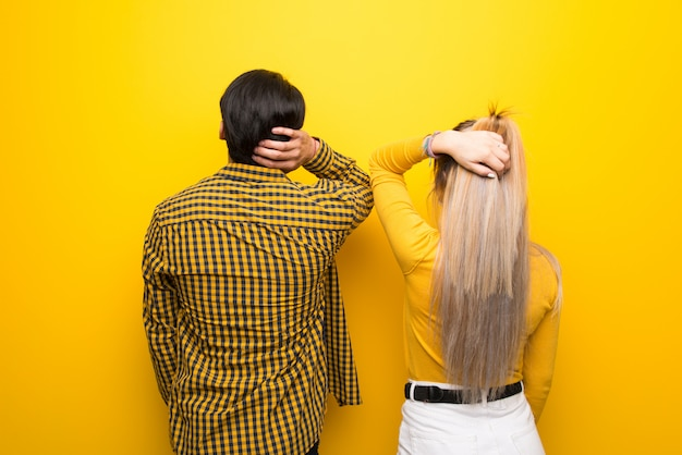Young couple over vibrant yellow background on back position looking back