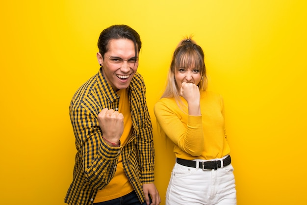 Young couple over vibrant yellow background celebrating a victory