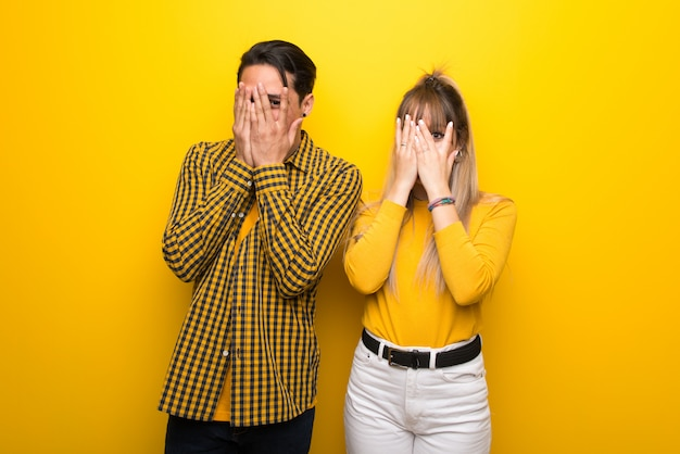 Young couple over vibrant yellow background covering eyes by hands