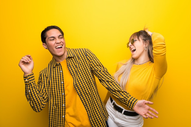 Young couple over vibrant yellow background enjoy dancing