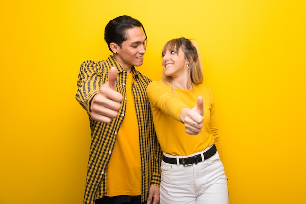 Young couple over vibrant yellow background giving a thumbs up