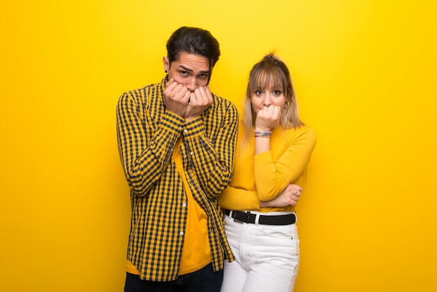 Young couple over vibrant yellow background is a little bit nervous and scared