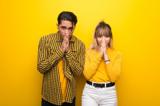 Young couple over vibrant yellow background keeps palm together