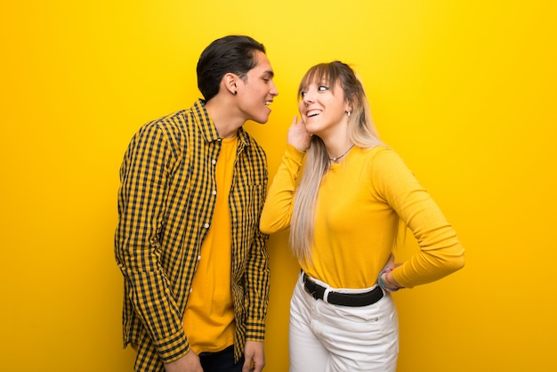 Young couple over vibrant yellow background listening to something