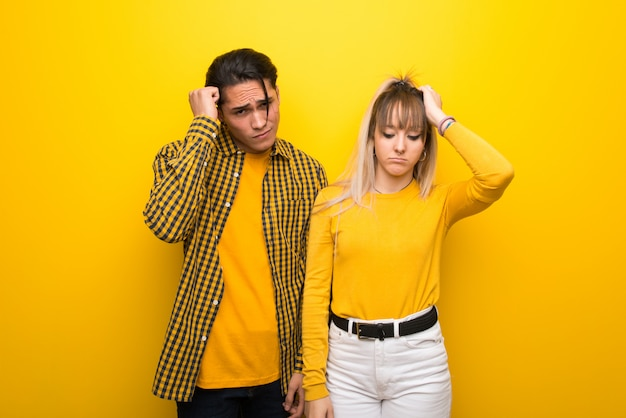 Young couple over vibrant yellow background with an expression of frustration
