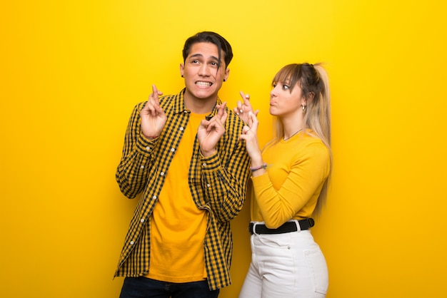 Young couple over vibrant yellow background with fingers crossing